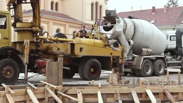 Beton pumpt zwischen Lastwagen zum Fundament.