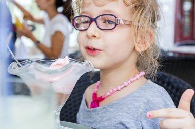 Little girl is eating ice cream at restaurant.