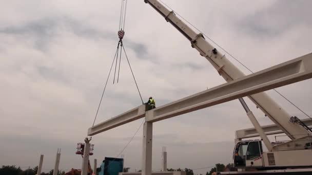Höhenarbeiter legt Dachstuhl auf Baugerüst.
