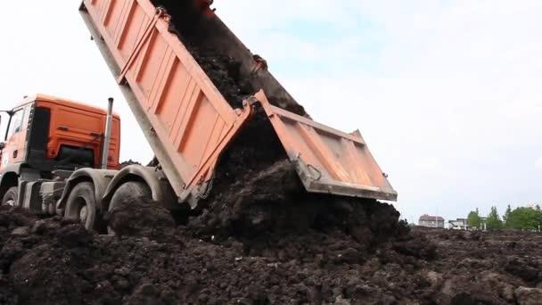 Sok dump teherautók a kirakodás az ugyanazt a kupac talajban.