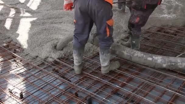 Dělníci jsou šíří betonu po velkých zesílené podlahy na staveništi.
