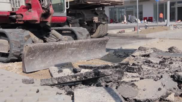 Bulldozer with bucket removes broken asphalt, close up.
