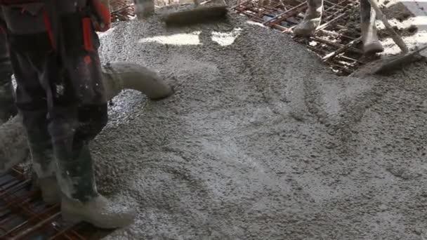 Dělníci jsou šíří betonu po velkých zesílené podlahy na staveništi