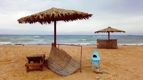 písečná pláž se slaměnými slunečníky a dřevěnými lehátky u moře