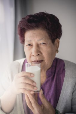 Asian senior woman holding a glass of milk, health concept.