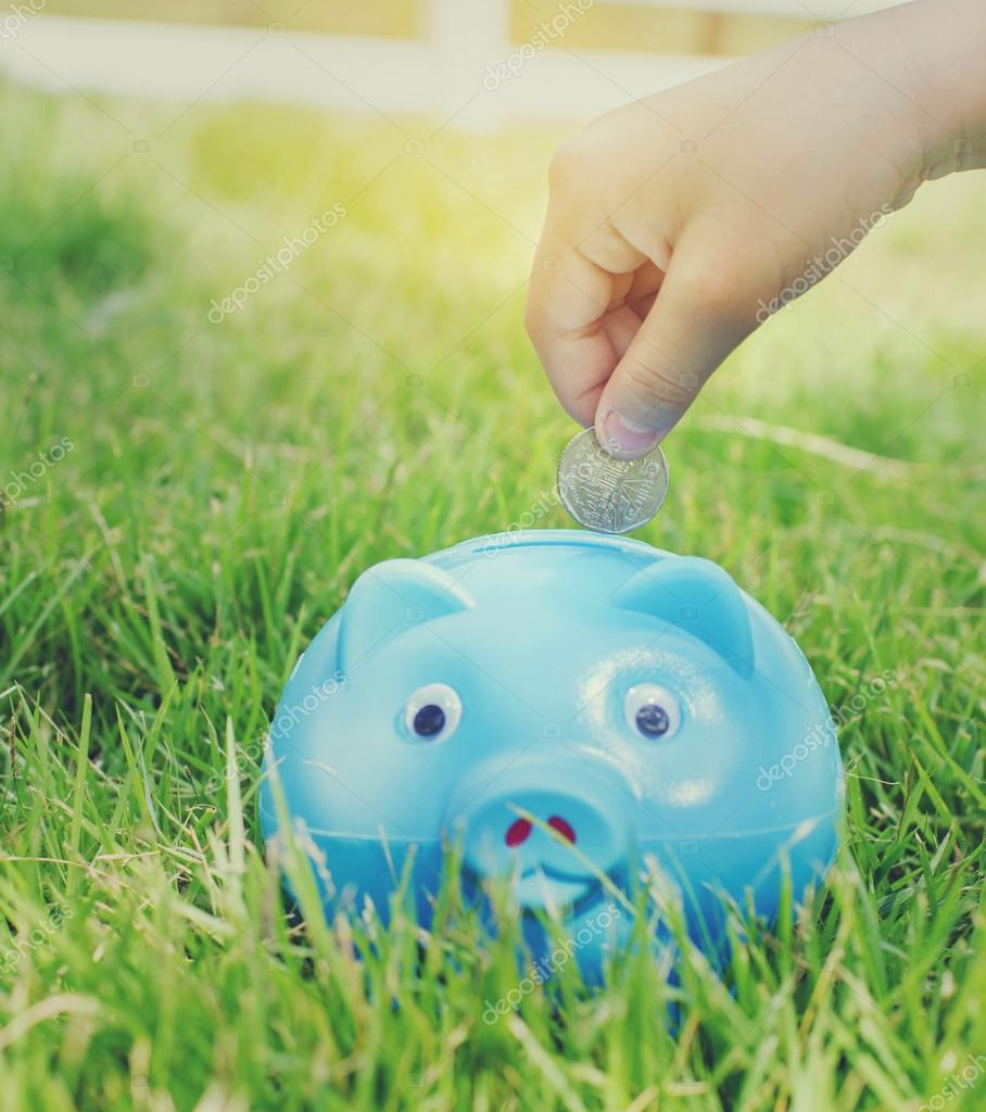 Blue piggy bank sitting on grass with hand putting Thai money.