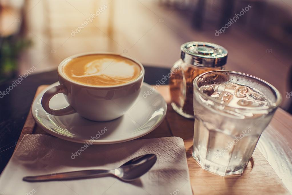 Coffee mug with brown sugar and glass of water set on wooden boa