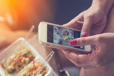 Close up of woman hands clicking picture of food. Woman using sm