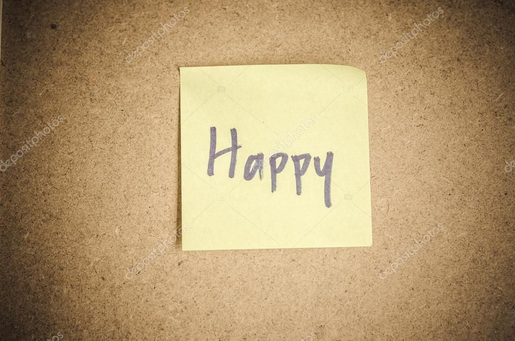 Happy note message on sticky paper by corkboard.