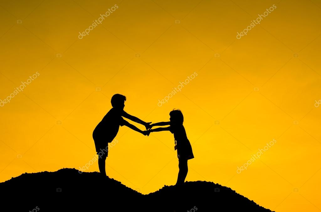 Two children during sun set, holding hands together.