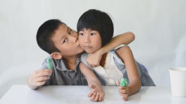 Boy kissing his sister