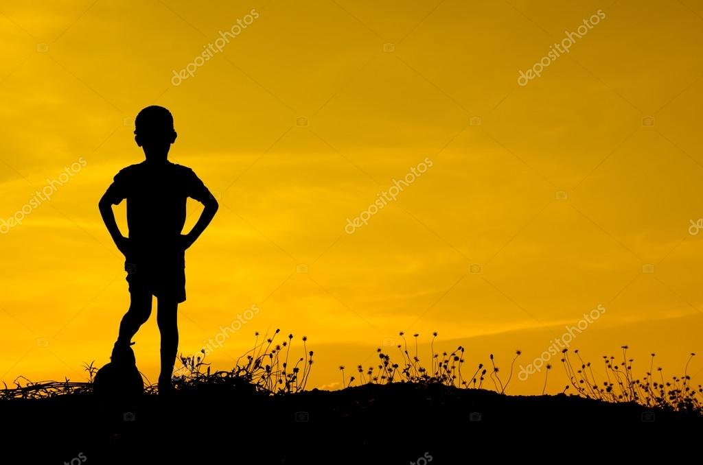 Silhouette of boy playing ball with sun set.