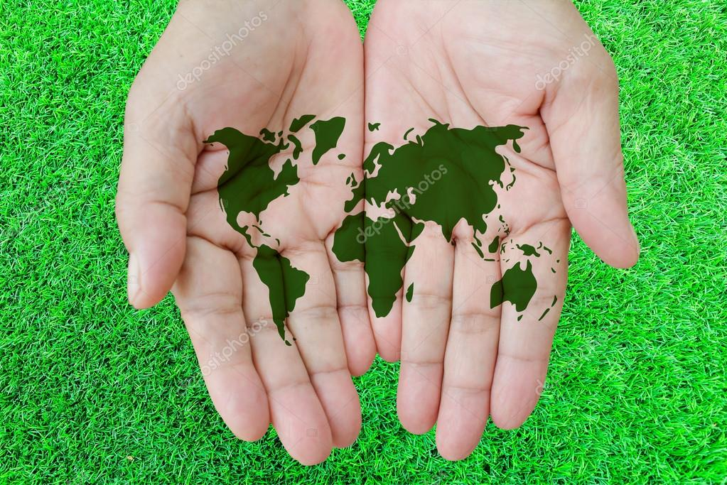 World Map On Hands.World Map In Hands With Grass Background Stock Photo