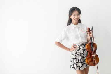 Asian teenager playing violin next to window, emotion concept.