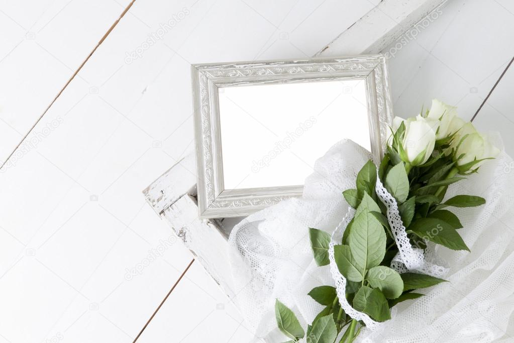 Leere silbernen Bilderrahmen mit fünf weißen Rosen und Spitzen-Band ...
