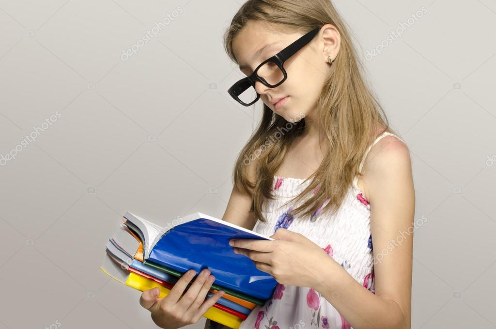Little girl with eyeglasses reading some books, kid learning, child studying