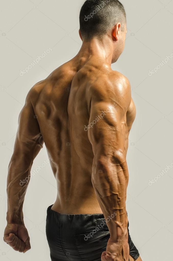 culturista mostrando su espalda, hombros, tríceps y bíceps músculos ...