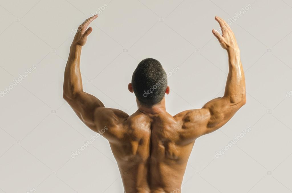Bodybuilder zeigen seinen Rücken, Schultern, Trizeps und Bizeps ...