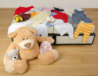 Bear toy on a bed with different colorful new born clothes.Colorful wardrobe of newborn,kids, babies full of all clothes, shoes,accessories and toys