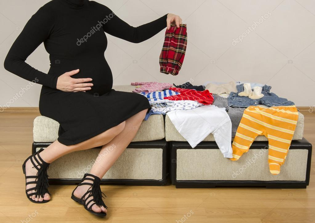 Pregnant woman looking at newborn clothes for her future baby, mother searching her new wardrobe for her infant