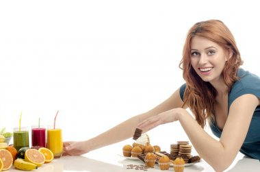 Woman choosing between fruits, smoothie and organic healthy food against sweets, sugar, lots of candies, unhealthy food. Treating your sweets addiction with fruits and vegetables