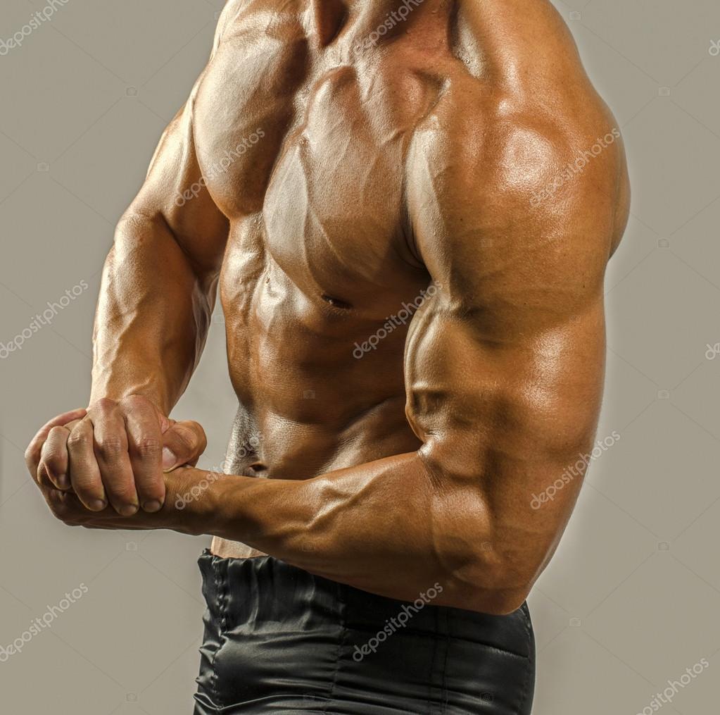 Culturista topless, flexionando sus bíceps. Hombre fuerte con abs ...