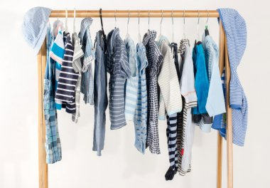 Dressing closet with clothes arranged on hangers.Blue and white wardrobe of newborn,kids, toddlers, babies full of all clothes.Many t-shirts,pants, shirts,blouses,blue hat, onesie hanging