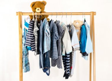 Dressing closet with clothes arranged on hangers.Wardrobe of newborn,kids, toddlers, babies full of all clothes.Many t-shirts,pants, shirts,blouses, onesie on a rack, bear toy hanging