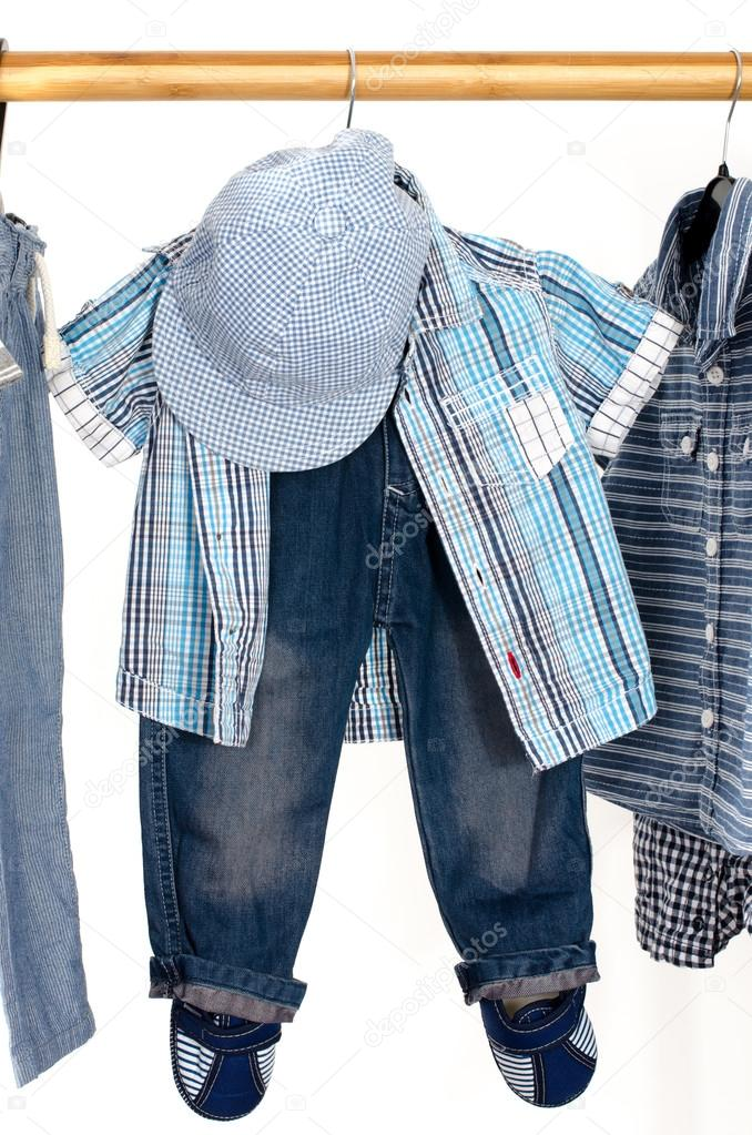 Dressing closet with clothes arranged on hangers.Blue and white wardrobe of newborn,kids, toddlers, babies full of all clothes.T-shirts,pants, shirts,blue hat hanging
