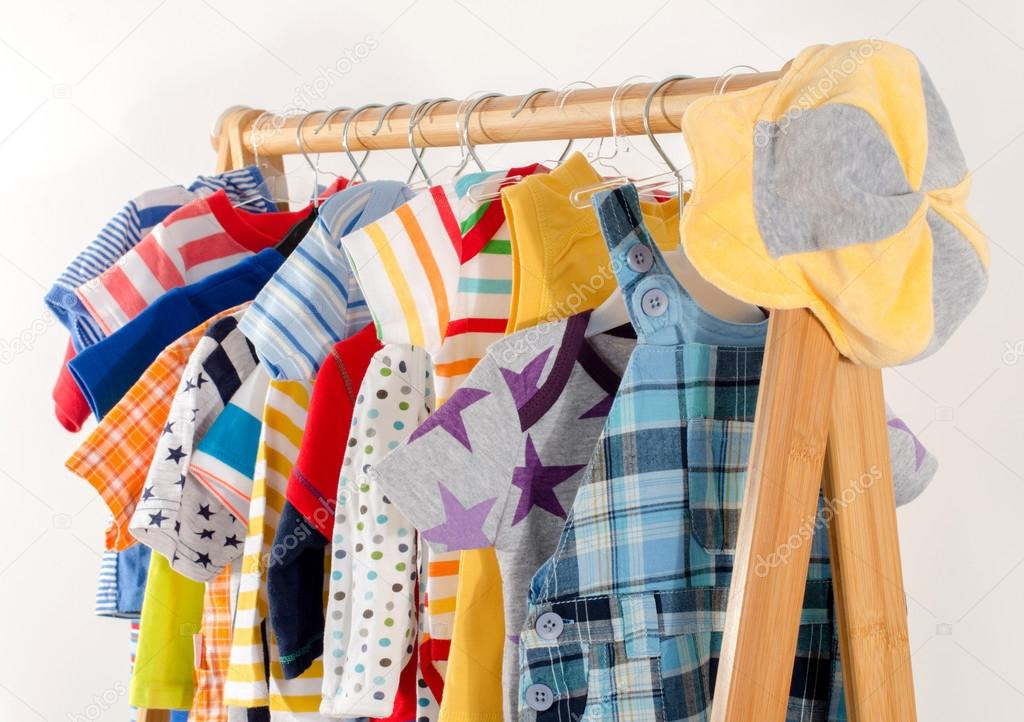 Dressing closet with clothes arranged on hangers.Colorful wardrobe of newborn,kids, toddlers, babies full of all clothes.Many t-shirts,pants, shirts,blouses,yellow hat, onesie hanging