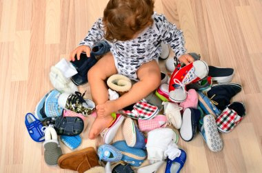 Toddler playing with a lot of baby shoes.