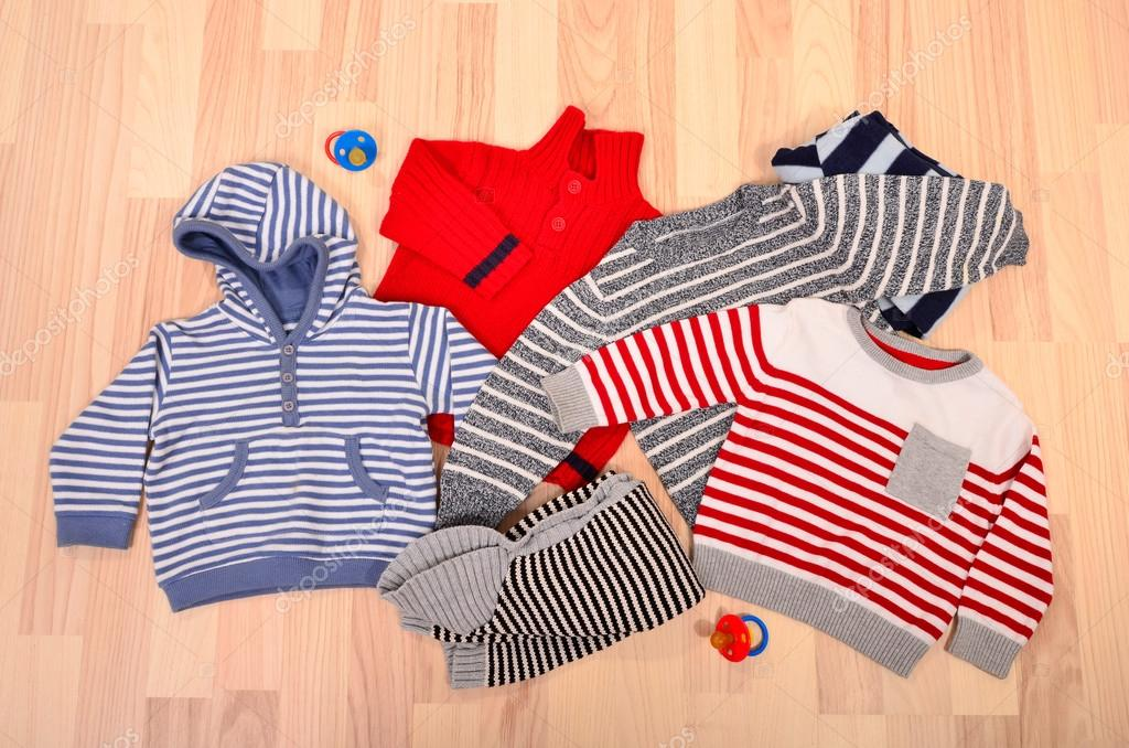 c09145955 Baby clothes lying on the floor. Winter child sweaters arranged ...