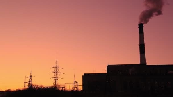 Heizkraftwerk mit einem Rohr, aus dem vor dem Hintergrund des abendlichen Hochglanzhimmels Dampf austritt. Gesamtplan