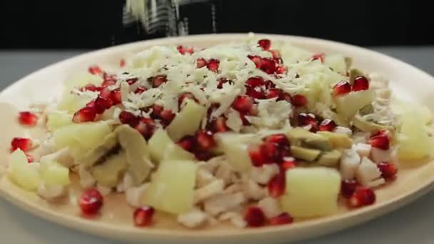 A womans hand pours parmesan cheese into a plate with a salad of chopped chicken fillet and mushrooms and pineapples. Medium plan