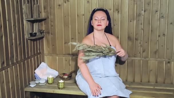 Eine Frau in einem Badetuch mit blauen Afro-Zöpfen fächert sich mit einem duftenden Lorbeerbesen auf. Gesamtplan