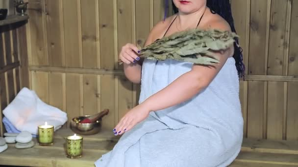 A woman in a bath in a towel without a face fanns herself with a fragrant laurel broom