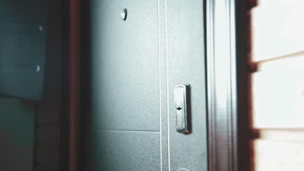 muž vyjde ze dveří, zasune klíč do klíčové dírky a zamkne ho