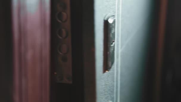 Žena vyjde ze dveří, zasune klíč do klíčové dírky a zamkne. Střední plán