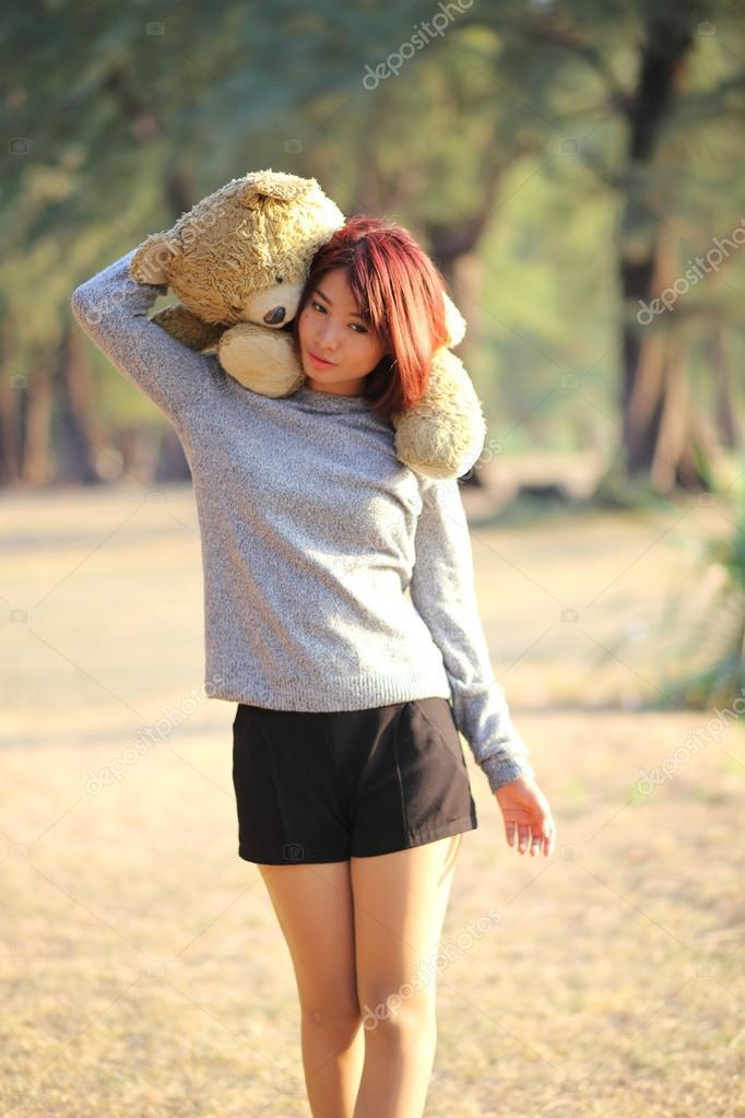Süße asiatische Mädchen halten Teddy nackt in den Park