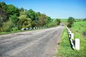 Asphalt road broken in field