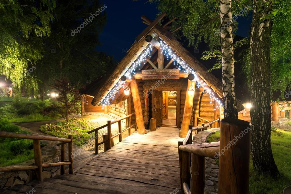 Wooden cottage in forest lit by lanterns