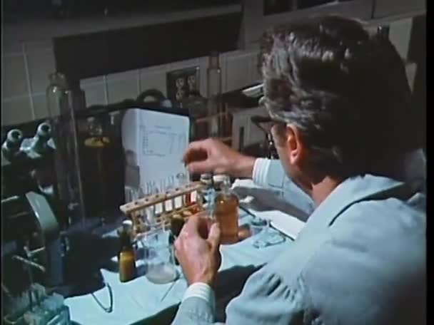 Scientist filling test tube with chemicals
