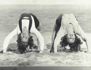 women doing backbends on the beach