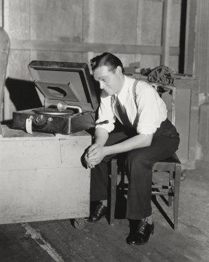 Mid adulMan listening to portable gramophone stock vector