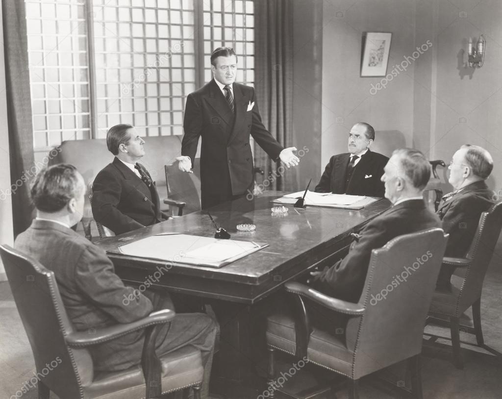 businessmen talking in board room