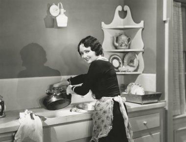 woman washing pots and pans