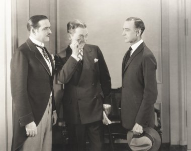 three men standing indoors