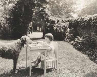 Child and dog face to face outdoors