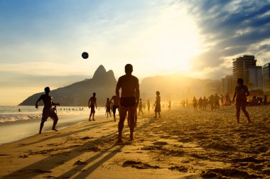 Rio de Janeiro beach football silhouettes of Brazilians playing keepy uppy altinho soccer on the sunset shore at Posto Nove Ipanema Beach stock vector