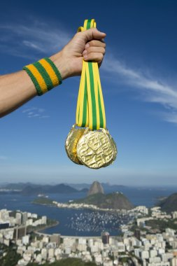 Hand of Athlete Holding Gold Medals Rio Skyline